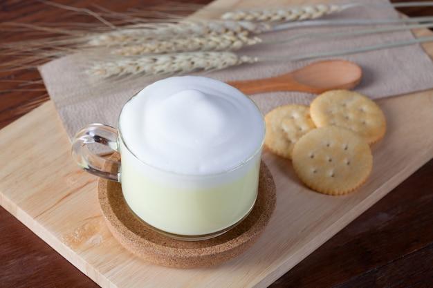 Закрыть горячего зеленого молока с печеньем на деревянной табличке на деревянный стол на завтрак.