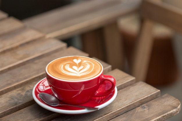 Close-up of hot latte coffee in a red cup on wooden table.