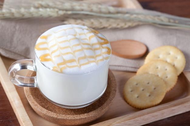 Закройте горячее молоко и карамель сверху с печеньем на деревянной тарелке на деревянном столе на завтрак.