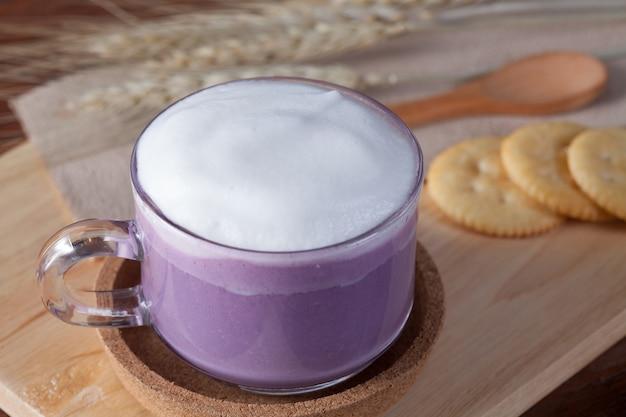 Закрыть горячее фиолетовое молоко с печеньем на деревянной тарелке на деревянный стол на завтрак.