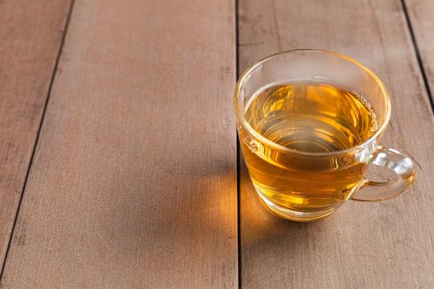 Закройте чашку горячего чая на деревянном столе. горячий чай в ручке стакана.