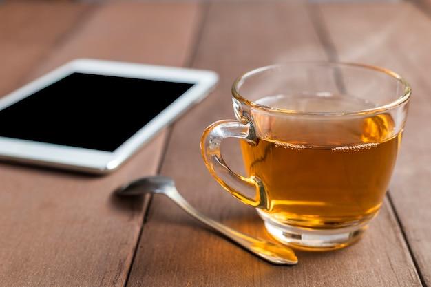 Закройте чашку горячего чая на деревянном столе с чайной ложкой и таблеткой в утреннее время