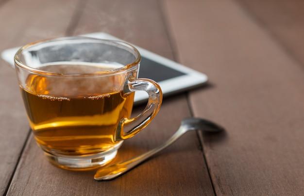 Закройте чашку горячего чая на деревянном столе с чайной ложкой и таблеткой
