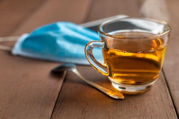 Закройте чашку горячего чая на деревянном столе с чайной ложкой, медицинской маской для лица и таблеткой