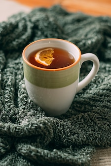 Close-up of hot tea with orange on scarf