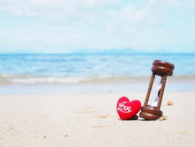 Close up hourglass and cushion heart shape with word love on summer beach.