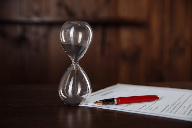 Close-up of hourglass measuring time, official signing contract.