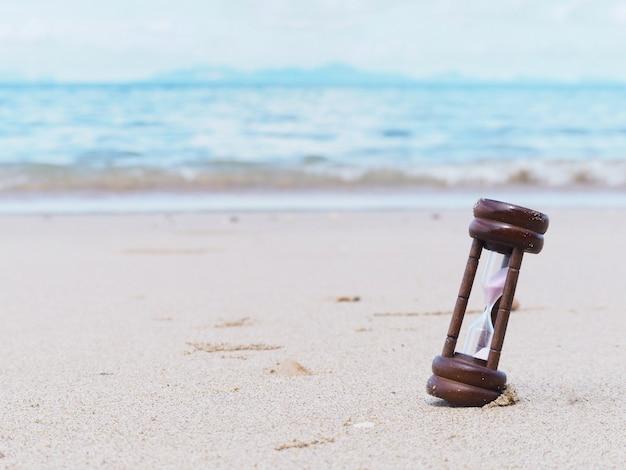Close up hourglass on summer beach.