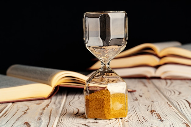 Close up of hourglass with books
