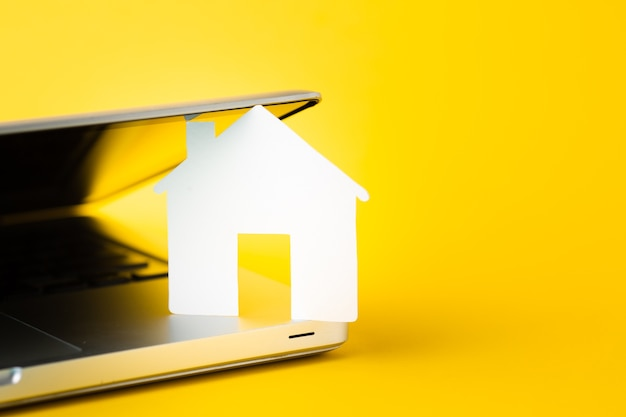 Close-up house figure with laptop concept
