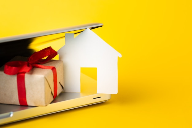 Close-up house figure with present and laptop