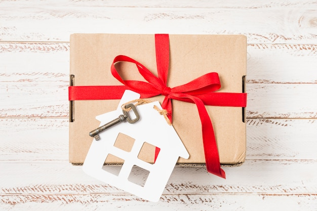 Close-up of a house key tied with red ribbon on brown gift box over painted wooden desk