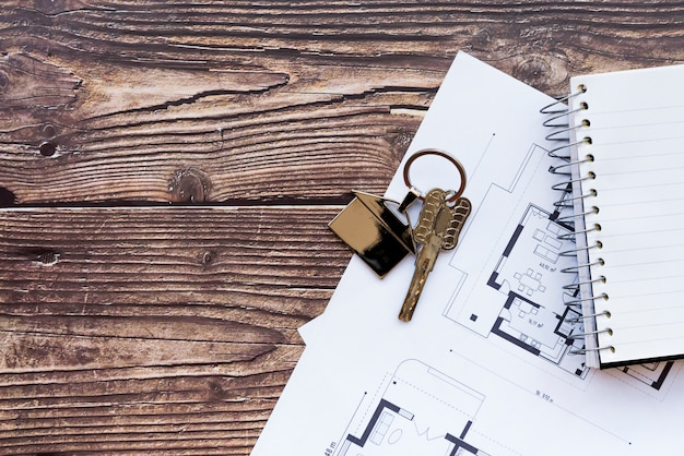 Close-up of house keys on blueprint of new home and spiral notebook on wooden textured backdrop
