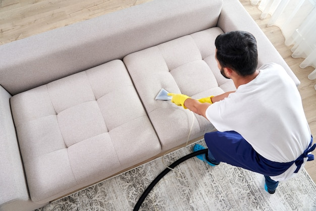 Close-up of housekeeper holding modern washing vacuum cleaner and cleaning dirty sofa with professionally detergent. professional springclean at home concept