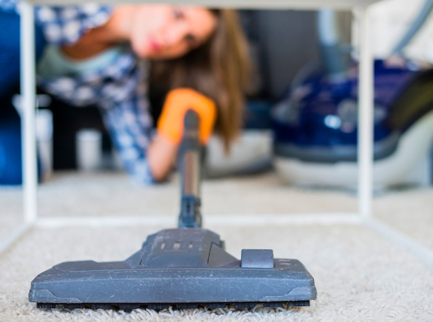 Close-up of a housemaid cleaning carpet with vacuum cleaner