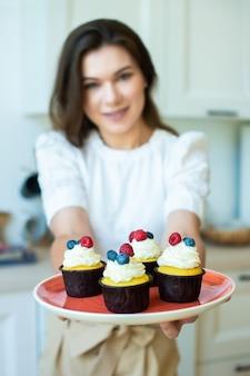 閉じる。主婦は微笑んで、色付きのベリー、ラズベリー、ブルーベリーのマフィンを手に持っています。家庭でのライフスタイル料理。休息の日