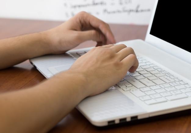 나무 책상에 노트북의 흰색 키보드에 입력 바쁜 인간의 손을 닫습니다.