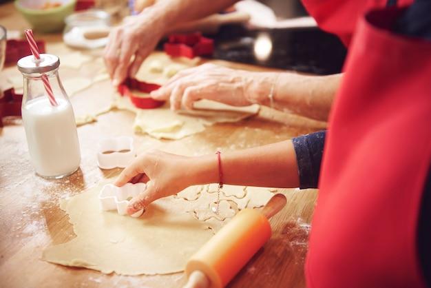 Chiuda in su della mano umana che taglia i biscotti