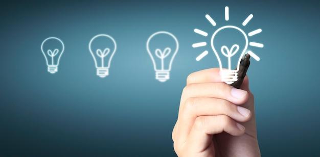 Close up human hand drawing light bulb