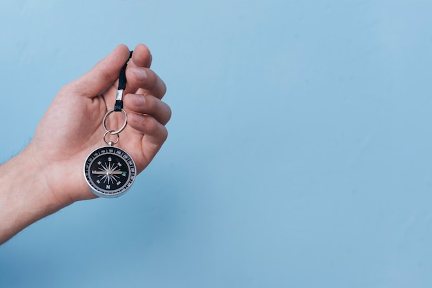 Close-up of human hand holding navigational compass on blue backdrop