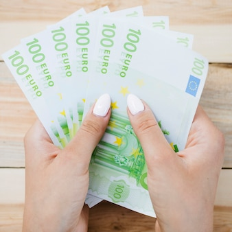 Close-up of human hand holding one hundred euro banknotes on wooden table