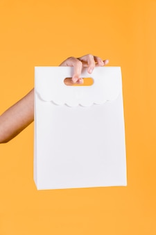 Close-up of human hand holding white paper bag on yellow wall backdrop