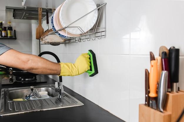 노란색 고무장갑을 끼고 인간의 손을 닫고 부엌 방의 타일 벽을 문지르기 위해 플라스틱 브러시를 사용하고 있습니다.