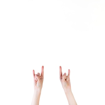 Close-up of a human hand making rock sign on white background