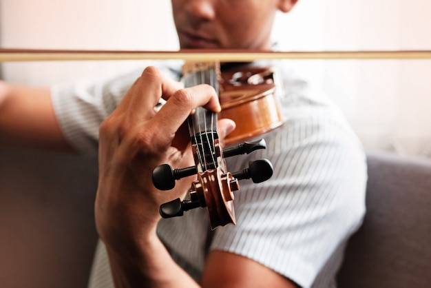 Close up human hand pressing string of violin, show how to play the instrument