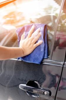 Close up human hand washing car