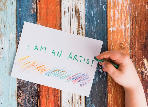 Close-up of human hand writing 'i am an artist' text on white paper with green crayon