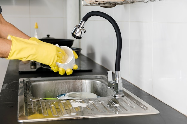 부엌 싱크대에서 세라믹 커피 머그를 세척하는 노란색 고무 장갑에 인간의 손을 닫습니다.