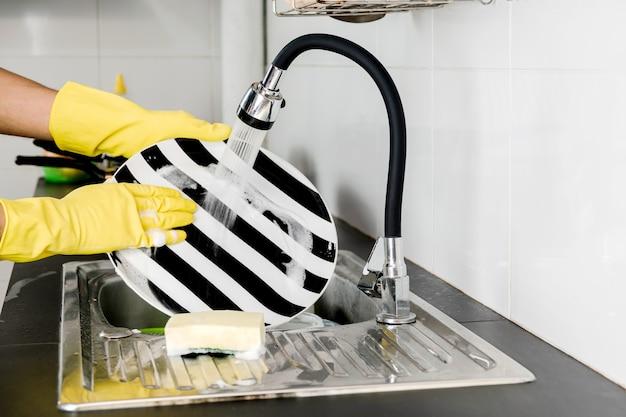 부엌 싱크대에서 설거지를 하는 노란색 고무 장갑에 인간의 손을 닫습니다.