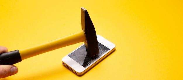 Крупным планом хаммер сокрушает осыпь смартфона, разрушенное устройство