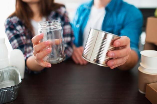 閉じる。夫と妻は2つのブリキ缶を手に持っています。若いカップルが台所でゴミを分類します。若い男性と女性がリサイクル可能なものを分類しています。
