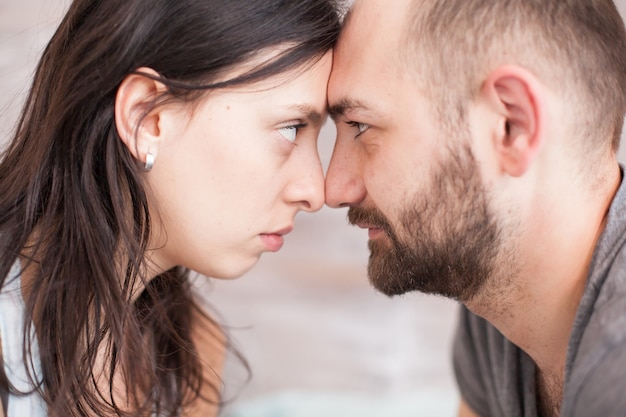 Close up of husband and wife looking into each other eyes in the morning.