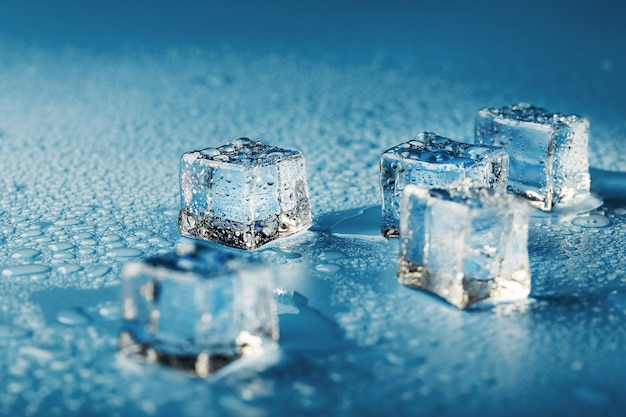 青いテーブルに散らばっている溶けた水滴のクローズアップ角氷。大きい。暑くて蒸し暑い日に飲み物やカクテルを楽しむためのさわやかな氷。