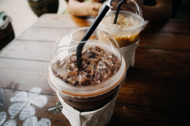Close up of iced coffee and cocoa drink in plastic cup on wooden table.