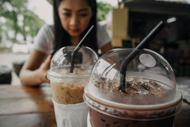 Close up of iced coffee and cocoa drink in plastic cup.