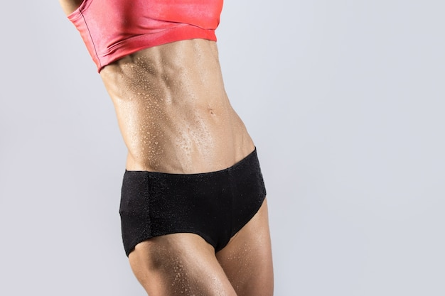Close-up of ideal sexy sweating abs of beautiful athletic woman