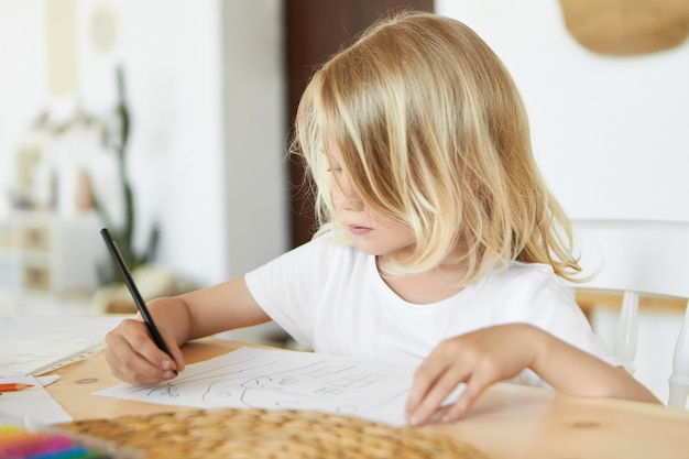 Close up image of adorable little boy with beautiful loose blond hair spending nice time after school, sitting at table with black pencil, drawing something, having focused concentrated expression