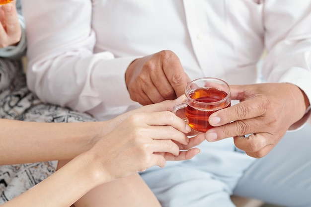 Close-up image of adult daughter giving small cup of black tea to senior father visiting her family for lunar new year celebration