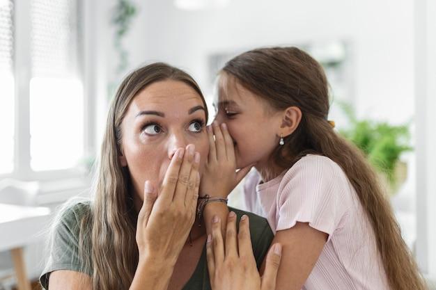 クローズアップ画像驚いた母親は小さな娘から信じられないほどのニュースを聞き、子供の女の子は秘密を共有し、ママは口を開けて驚き、信頼、自信を持って、楽しいコンセプトを感じます