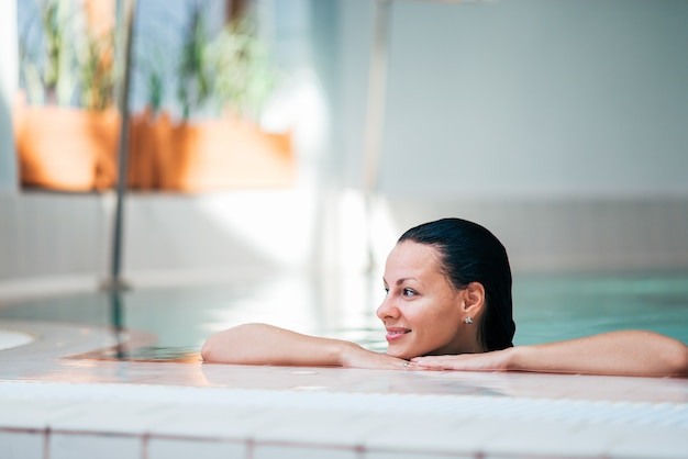 Close-up image of a beautiful woman relaxing in a swimming pool.