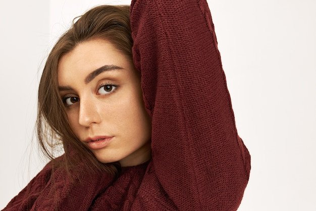 Close up image of beautiful young european female with clean fair skin and dark hair wearing stylish warm knitted sweater raising her arm, staring at camera with serious confident facial expression