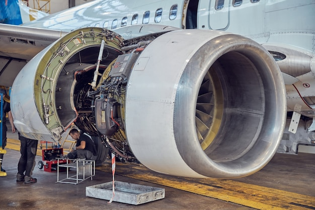 Close up image of big open turbine with wing on the scheduled modernization of passenger airplane in the aerodrome