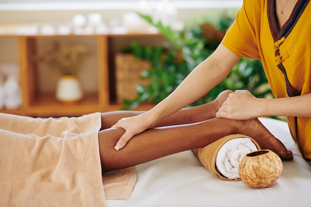 Close-up image of black young woman getting relaxing legs massage in beauty salon and applying pressure with thumb on calf muscle