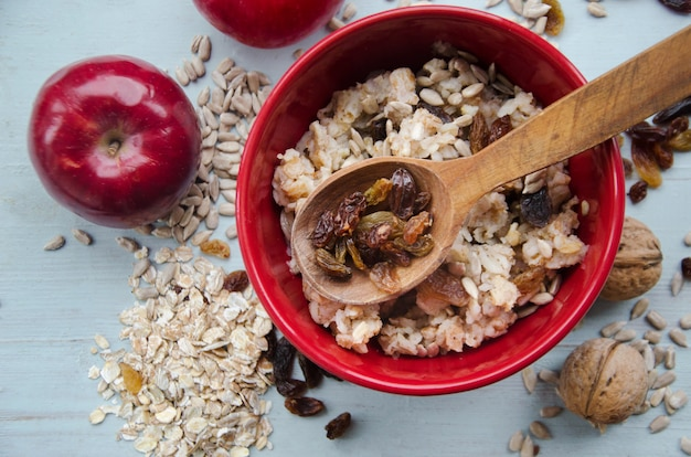 Close up image of bowl of healthy gluten free oatmeal with nuts and raisins