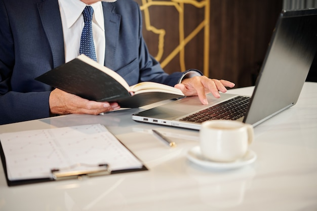 Close-up image of businessman checking planner and filling document on laptop