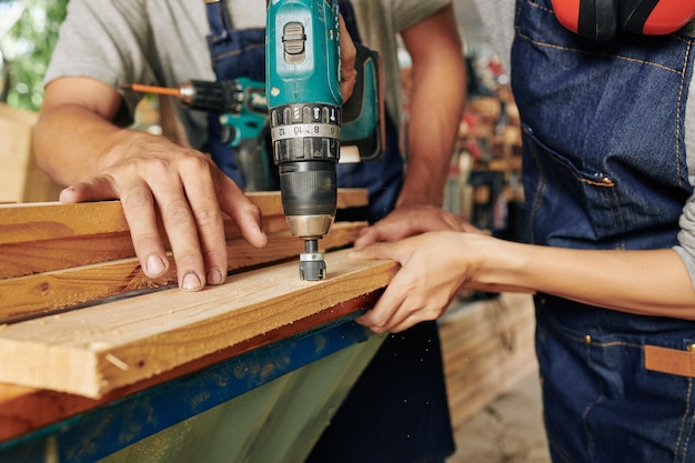 Close-up image of carpenter helping to hold wooden plank when his coworker drilling big hole